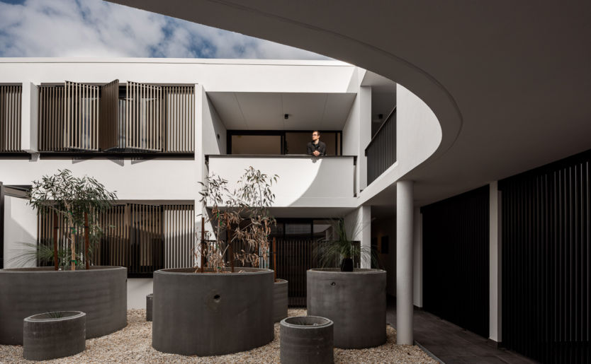Architectural and Artistic shot of M/28 Apartment by Match courtyard with a resident standing on the first floor balcony